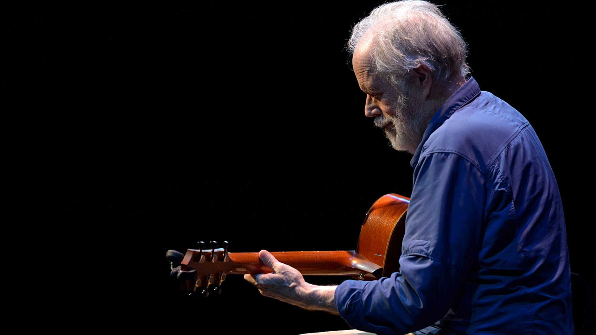 Leo Kottke beneath a spotlight on an darkened stage, working his stunning fingerpicking style on an acoustic guitar.