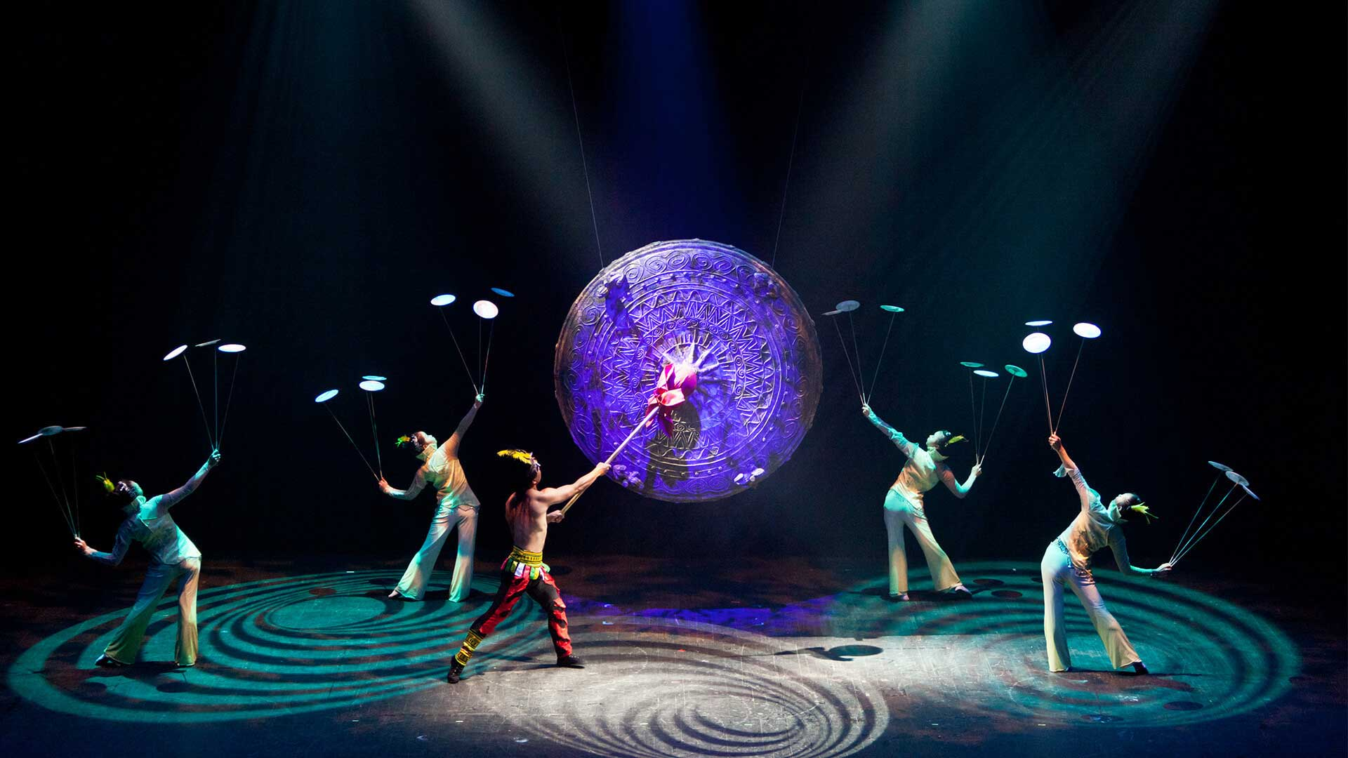 The Golden Dragon Acrobats perform feats of athleticism and artistry on a stage centered by a giant gong.