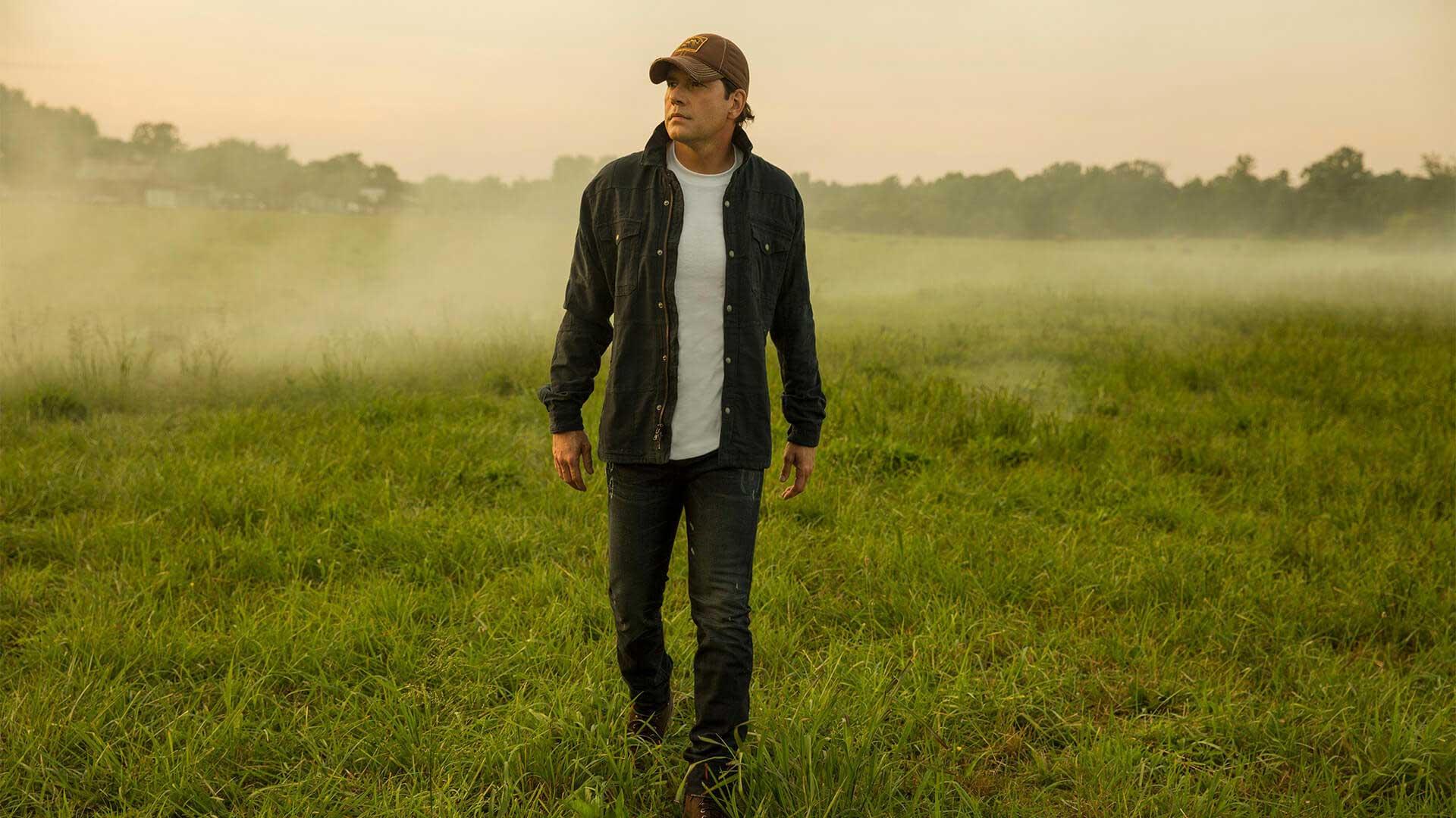Country music star Rodney Atkins walks across a foggy field.