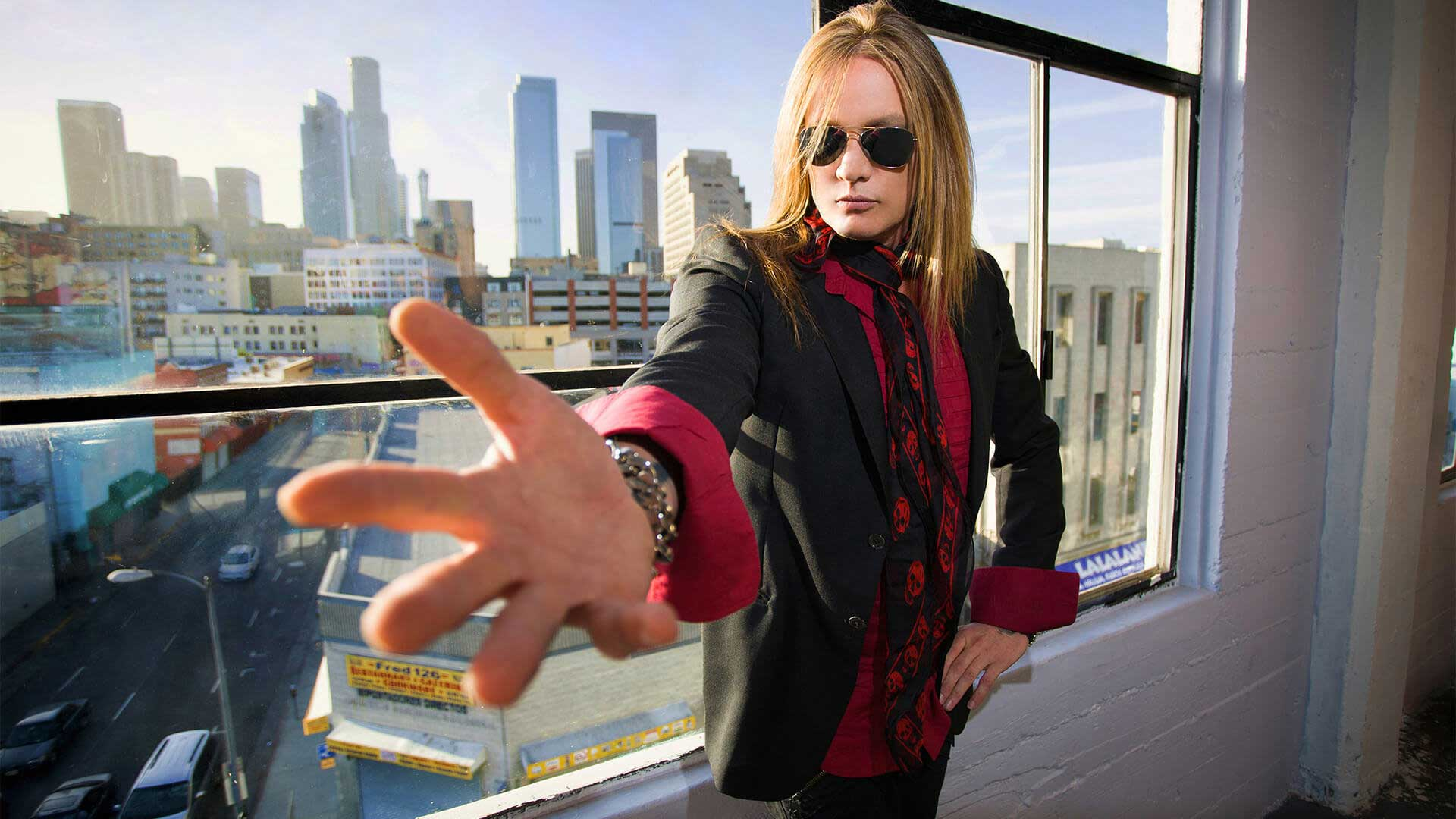 From a window overlooking a cityscape, frontman Sebastian Bach reaches out to beckon rock fans to his Paramount concert.