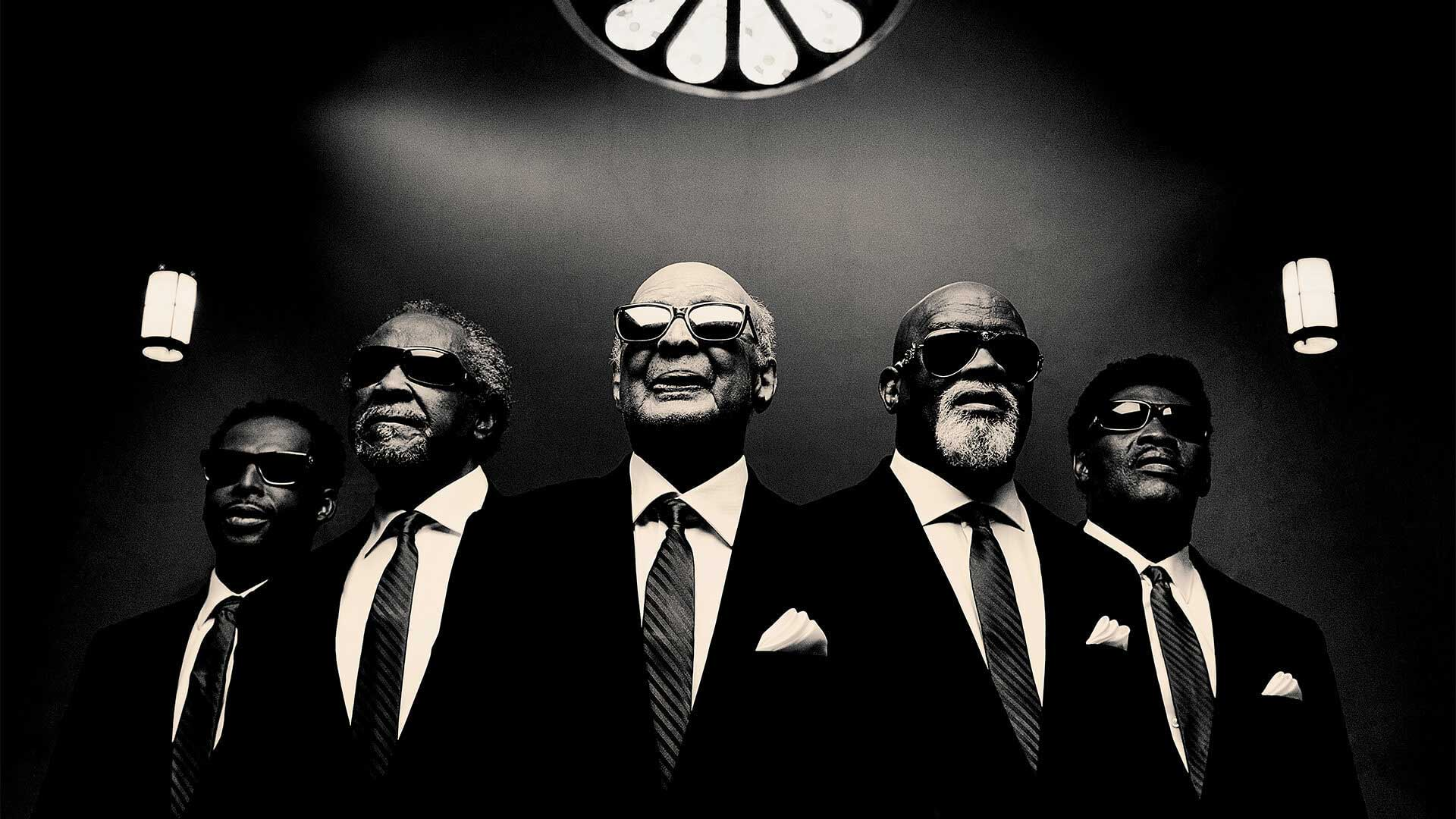 Dressed in black suits and sunglasses, five members of The Blind Boys of Alabama prepare to sing Gospel favorites.